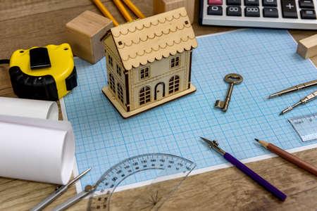 Photo pour Wooden house model with key on millimeter paper - image libre de droit