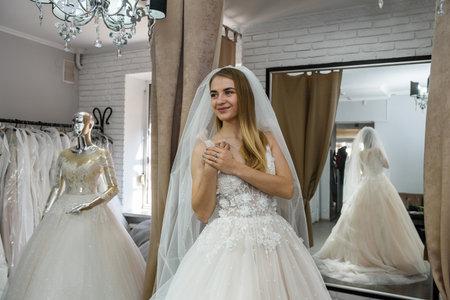 Photo pour Beautiful bride in wedding dress standing in boutique - image libre de droit