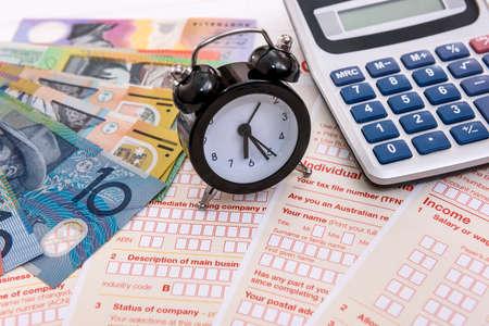 Foto de Australian dollars, clock and calculator on tax form - Imagen libre de derechos