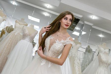 Photo pour Happy bride tries on a wedding dress in salon - image libre de droit