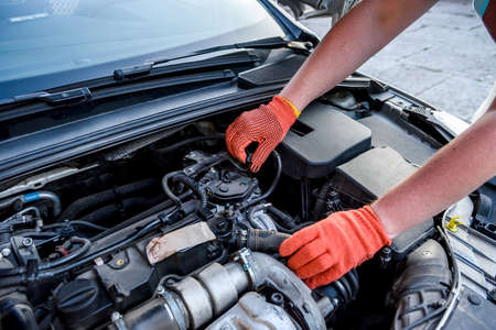 Photo for Hands in gloves with car engine close up - Royalty Free Image