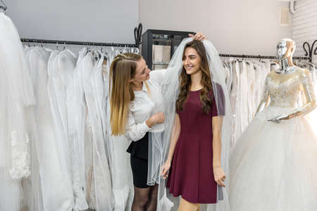 Photo for Bride with tailor choosing wedding dress in store - Royalty Free Image