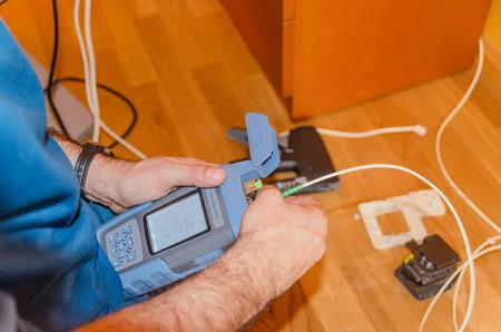 A technician measures the internet power after a fiber optic installation