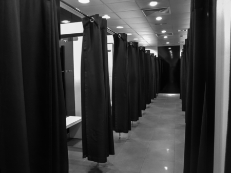 empty fitting room in a fashion shop. Shopping and consumerism concept