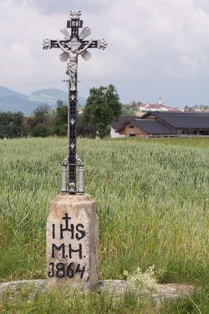 Field Cross of metal, behind a little rural community