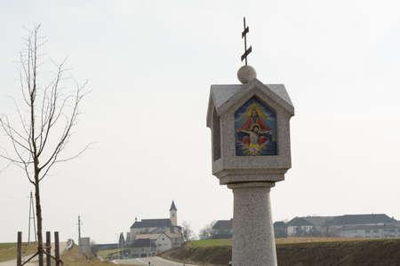 roadside shrine from granite in front of a rural community - - Austria