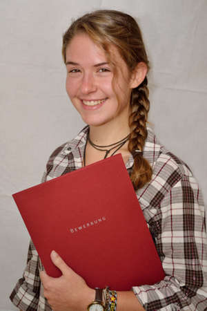 Young woman holding application papers in hands and laughs