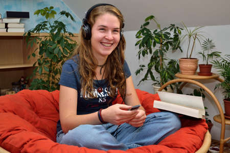 Teenager listening to music, looking forward and laughs