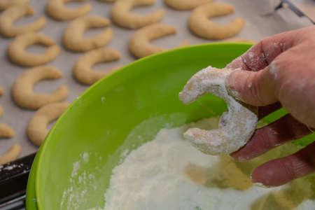 Tasty Christmas cheeses are prepared - vanilla croissants dip into dust sugar