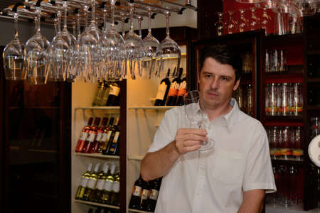 Wine glasses are tested by a hotel owner at the counter