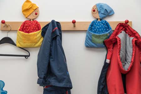 Photo pour Childrens wardrobe with child-friendly clothes hooks and kids jackets - close-up - image libre de droit