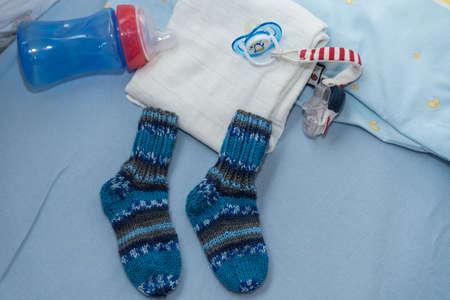 Photo pour Childrens room shows cozy corner with milk bottle, nipples and wool socks - close-up - image libre de droit