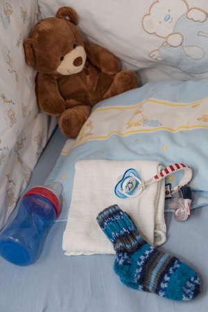 Photo pour Cosy corner in the nursery with pacifier, teddy bear and wool sock - image libre de droit