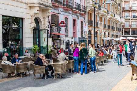 Photo for Huelva, Spain - April 1, 2021: People sitting in terrace of a cafe and bar in the square Plaza de las Monjas (Nuns square) of Huelva - Royalty Free Image