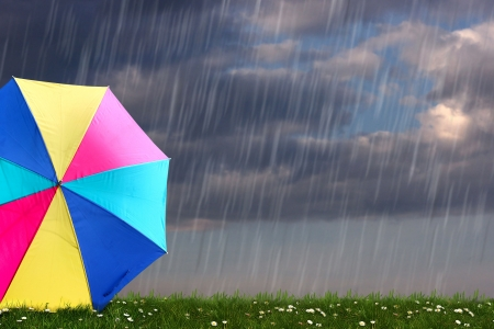 rainbow colored umbrella s in heavy rain to use as background の写真素材