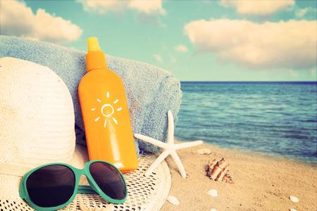 Straw hat,sunglasses, towel and starfish on sand beach.