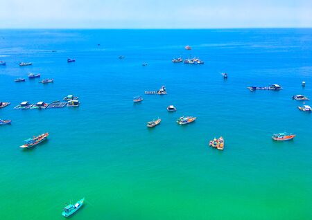 Photo for Traditional colorful fishing boats in the azure sea in Phu Quoc island, Vietnam. View from of a cable car. - Royalty Free Image