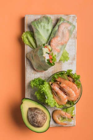 Spring rice paper roll with shrimp, avocado, paprika, lettuce and cottage cheese on a wooden white Board on an orange background. Vegan food. Top view. Vertical orientation.