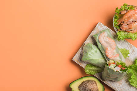 Spring rice paper roll with shrimp, avocado, paprika, lettuce and cottage cheese on a wooden white Board on an orange background. Vegan food. Top view with a copy space. Horizontal orientation.