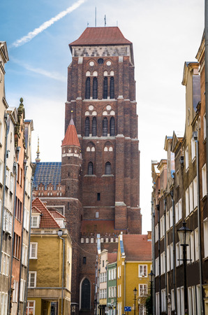 Brick tower of Basilica Assumption Blessed Virgin Mary St Marys Church Cathedral view from narrow street with typical colorful houses buildings in old historical town Gdansk, Poland
