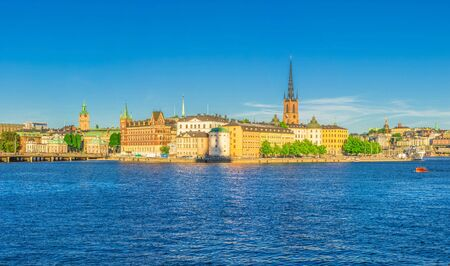 Panoramic view of Riddarholmen island district, Riddarholm Church spires, typical sweden colorful gothic buildings, Birger jarls torn, Lake Malaren water, blue clear sky background, Stockholm, Sweden