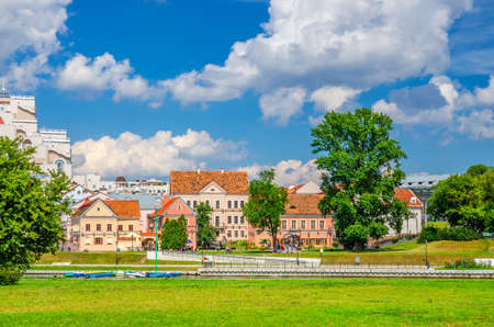 Photo for Traeckaje Suburb with old buildings in Trinity Hill district and grass lawn with green trees in Minsk city historical centre, blue sky white clouds in sunny summer day, Republic of Belarus - Royalty Free Image