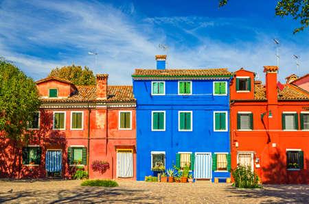Photo pour Colorful houses of Burano island. Multicolored buildings in small cobblestone square, blue sky background in sunny summer day, Venice Province, Veneto Region, Northern Italy. Burano postcard - image libre de droit