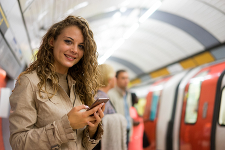 A woman using a mobile phone on the tube underground station, London
