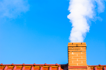 Photo for Modern house roof with chimney smoke, air pollution and smog in winter, ecological problems - Royalty Free Image