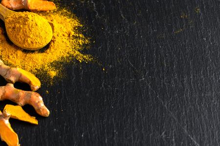 Foto de Fresh root and turmeric powder, indian spice, healthy seasoning ingredient for vegan cuisine - Imagen libre de derechos