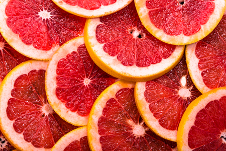 Foto de Sliced grapefruits, background, natural texture of citrus, top view, close-up - Imagen libre de derechos