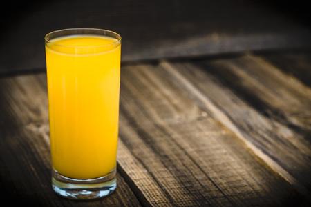 Foto per Fresh juice in a glass. Orange juice on wood. - Immagine Royalty Free