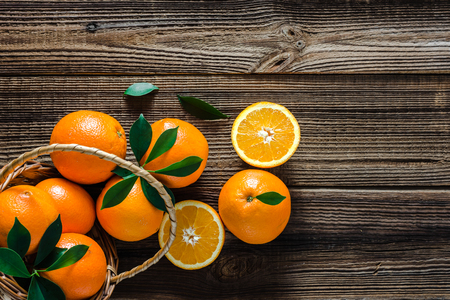 Foto de Basket with oranges on wooden background. Farm fresh orange on market. - Imagen libre de derechos