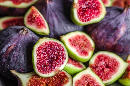 Foto de Fresh fig fruits. Slices of juicy red figs, background. - Imagen libre de derechos