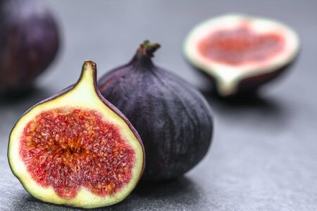 Foto de Fresh fig fruits. Whole and sliced figs on dark background. - Imagen libre de derechos