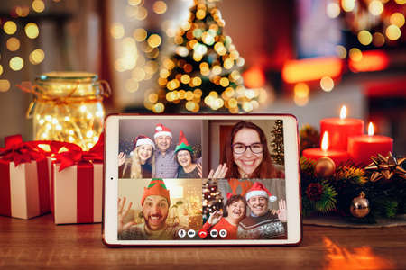 Photo pour Christmas video call with the family. Concept of families in quarantine during Christmas because of the coronavirus. Xmas still life with a tablet in a cozy room - image libre de droit