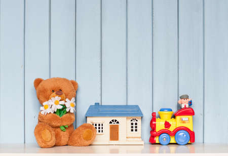 Foto de soft teddy bear with flowers, toy house and mechanical locomotive on the bookshelf on blue wooden background in the children's room - Imagen libre de derechos