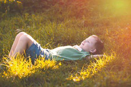 Child lies on green grass in sunny countryside, le petit prince
