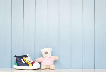 Foto de Tiny baby shoes and teddy bear on the table in baby's room - Imagen libre de derechos