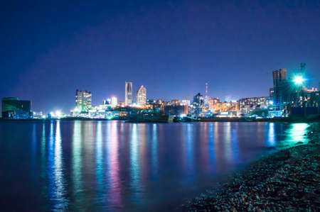 night sea sight with streets, buildings and street lights reflected in the sea, Vladivostok