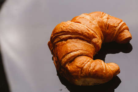 fresh croissant from the puff pastry on a black background.