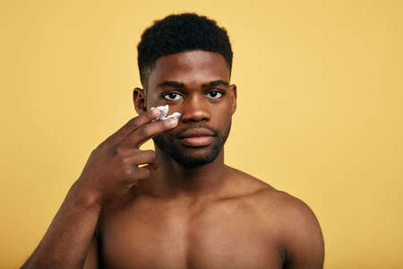 Photo pour shirtless young brutal african american man applying facial cream on his cheek. close up portrait,mens beauty. skin care - image libre de droit