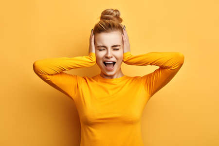 Foto de Young woman in stylish yellow sweater screaming in terror with hands on her head, mouth wide open. silence concept. stop talking. I hate you. emotion and feeling - Imagen libre de derechos