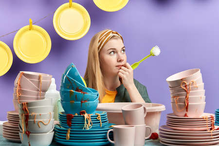 Photo pour young beautifulpensive thoughtful housewife holding a brush and sitting behind the table with a pile of dirty dishes, idea, plan concept - image libre de droit