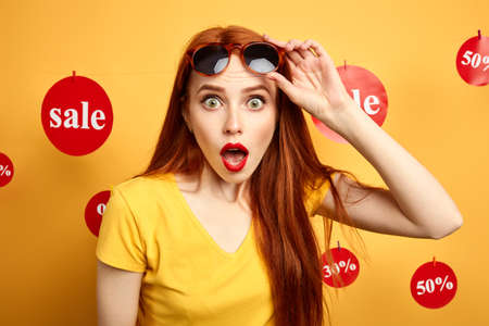 Photo pour girl with sunglasses on her forehead cannot believe in huge sales. close up photo. isolated yellow background, studio shot.surprise. shock concept, woman claims a discount - image libre de droit