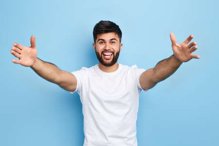 Photo pour happy handsome Arab bearded young man standing with raised arms, he wants to hug his friend, isolated on blue background.. I love you. I miss you.body language - image libre de droit