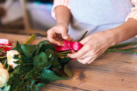 close up cropped photo of female florist making bunch and tying ribbon at flower shop.