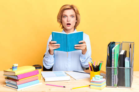 Photo pour surpride woman with wide open mouth holding a book, sitting at the des, preparing for exam, close up portrait, isolated yellow background, studio shot - image libre de droit
