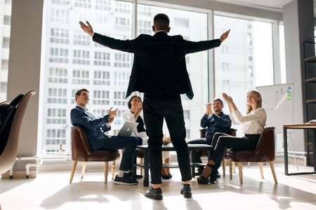 Photo pour business people sitting at table congratulating colleague with promotion, man with outstretched arms rejoicing at success, panorama window. you got it.we done it, back view photo. full length - image libre de droit