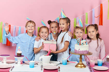 Foto de friendly smiling children holding a box with gift posing to the camera during the party, happiness, isolated pink background, studio shot. friendship - Imagen libre de derechos
